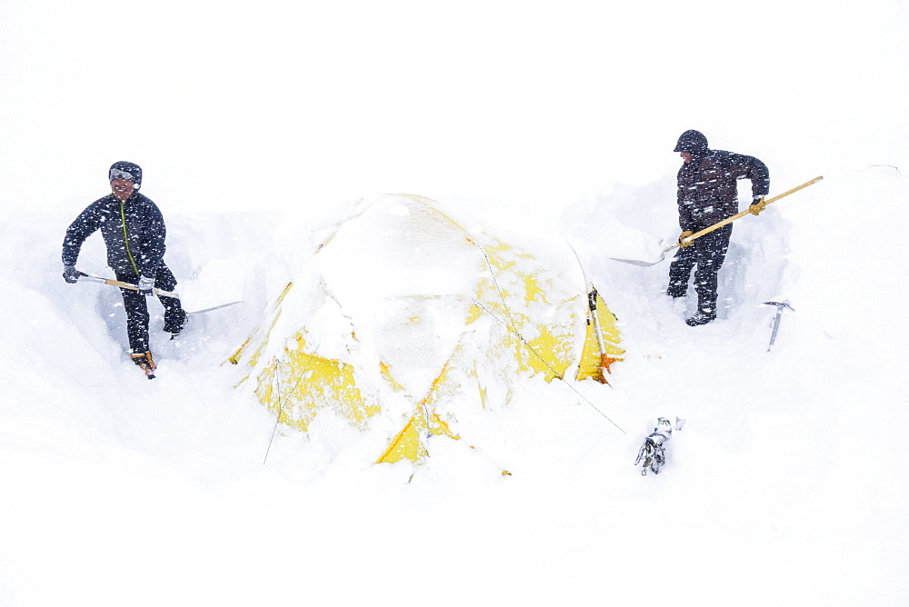 Two climbers dig out their tent after a snowstorm covered them in 14k camp on Mount McKinley, Alaska. Climbers are advised to spare no expense on a expedition-quality tent as it can mean the difference between life and death during a ferocious storm on Denali. Extra poles and repair materials are important in case of damage caused by storms. Plan to take extra pickets, wands or deadmen for tent anchors. Never leave a tent without anchoring it securely. Tents are lost each year due to sudden gusts of wind while the tent was left unattended or drying. Every climbing season High Mountain Rangers of the Denali National Park Service are called to help climbers in need. If possible the patient is brought down to base camp on foot, only in life threatening conditions a helicopter is called to evacuate the patient to a hospital in Anchorage.