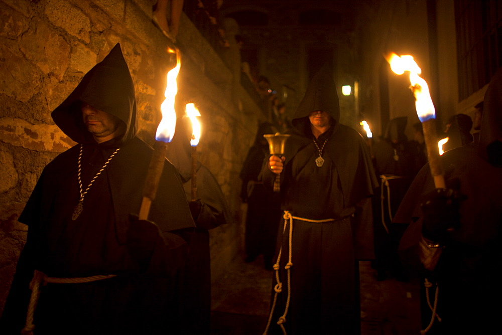 A penitent dressed as a Benedictine monk rings a bell surrounded by men carrying torches at the procession of the Black Christ of Santa Maria during Easter Holy Week inside of the Cathedral of Caceres, Extremadura, Spain