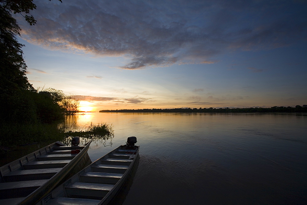 Two boats sit at the shore of the Amazon River in Peru at sunset.