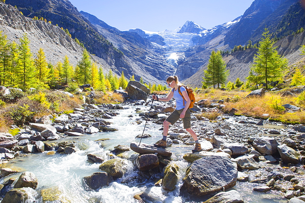 A female hiker crossing a river in the Swiss Alps. In the background is the Ried glacier. This region of Wallis, close to Zermatt, is a paradise for outdoor enthusiasts like climbers, alpinists, hikers, mountainbikers and nature lovers. The water is directly coming from the glacier, so very refreshing after an excercise.
