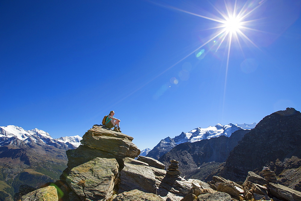 A female hiker sitting on top of the Wannihorn in the Swiss Alps. In the background the four thousand meter peaks of the Weisshorn and Weissmies. This region of Wallis is a outdoor paradise for all climbers, hikers, mountainbikers, trailrunners and nature lovers.