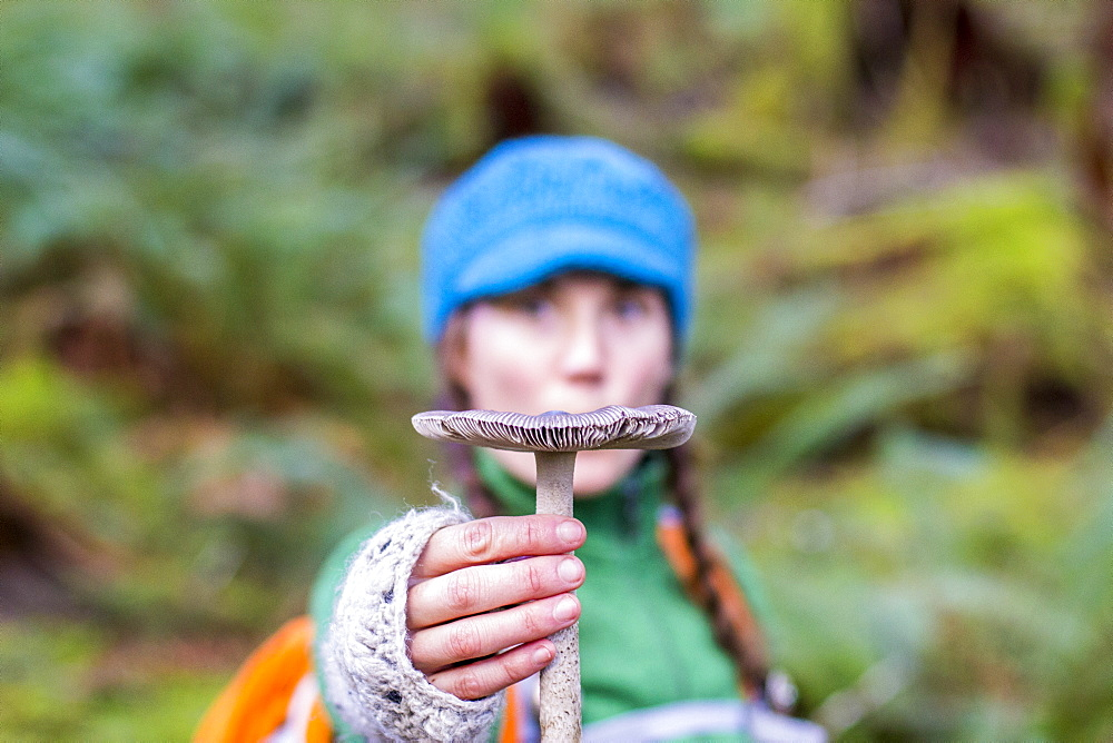 Woman holds up a mushroom in front of her face in the Hoh Rainforest, WA
