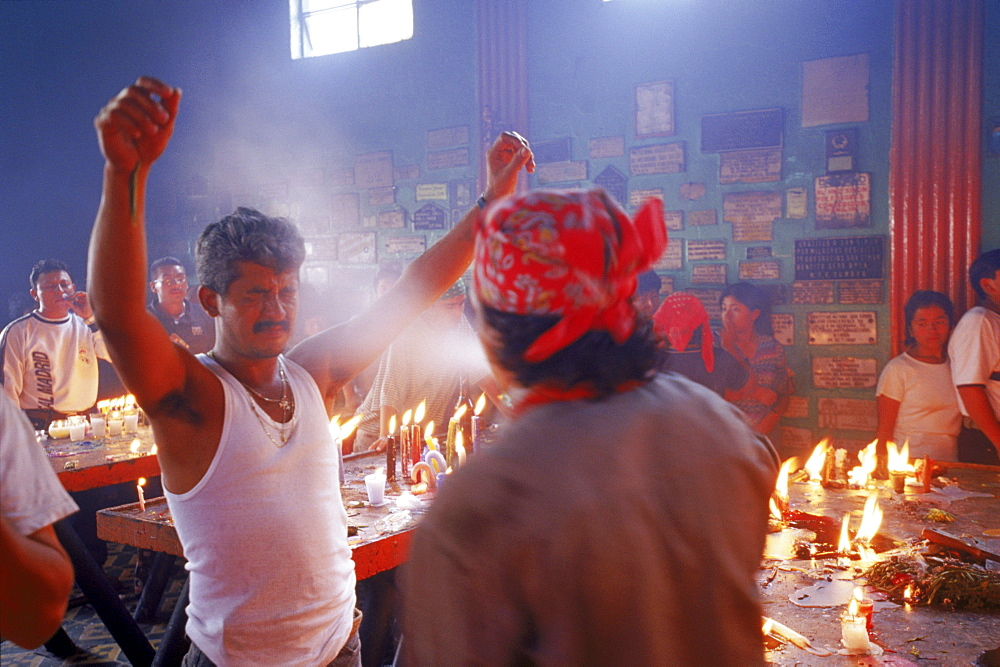 Priests douse worshipers with a spray of alcohol during a ritual blessing at a temple.
