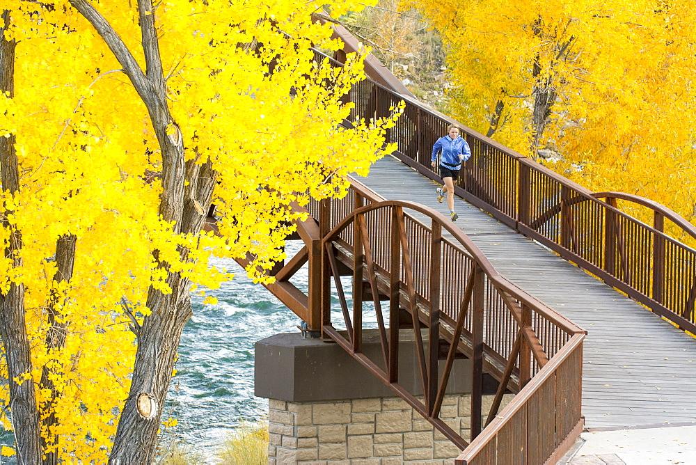 A woman running over the Animas River on a bridge on the Animas River Trail in Durango, Colorado.