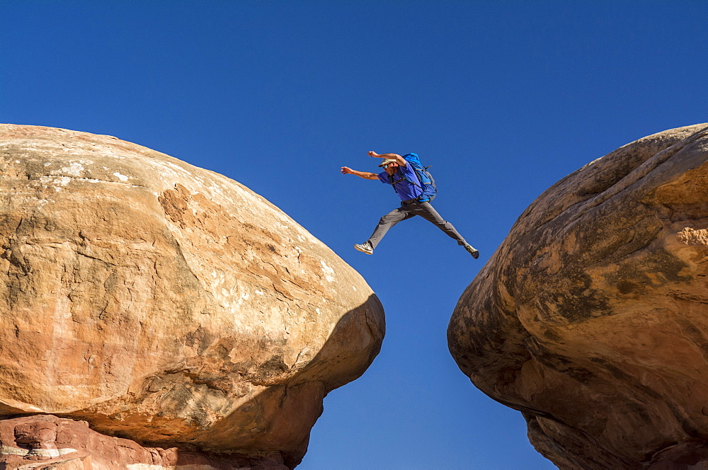 A man jumping between sandstone hoodoos along the Chessler Park and Joint Trail hike, Needles District, Canyonlands National Park, Monticello, Utah.