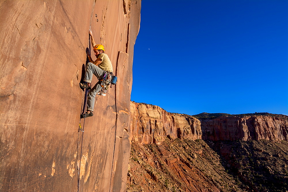 A man rock climbing up a difficult crack called Sig Sauer at the Pistol Whipped Wall in Indian Creek, Monticello, Utah.