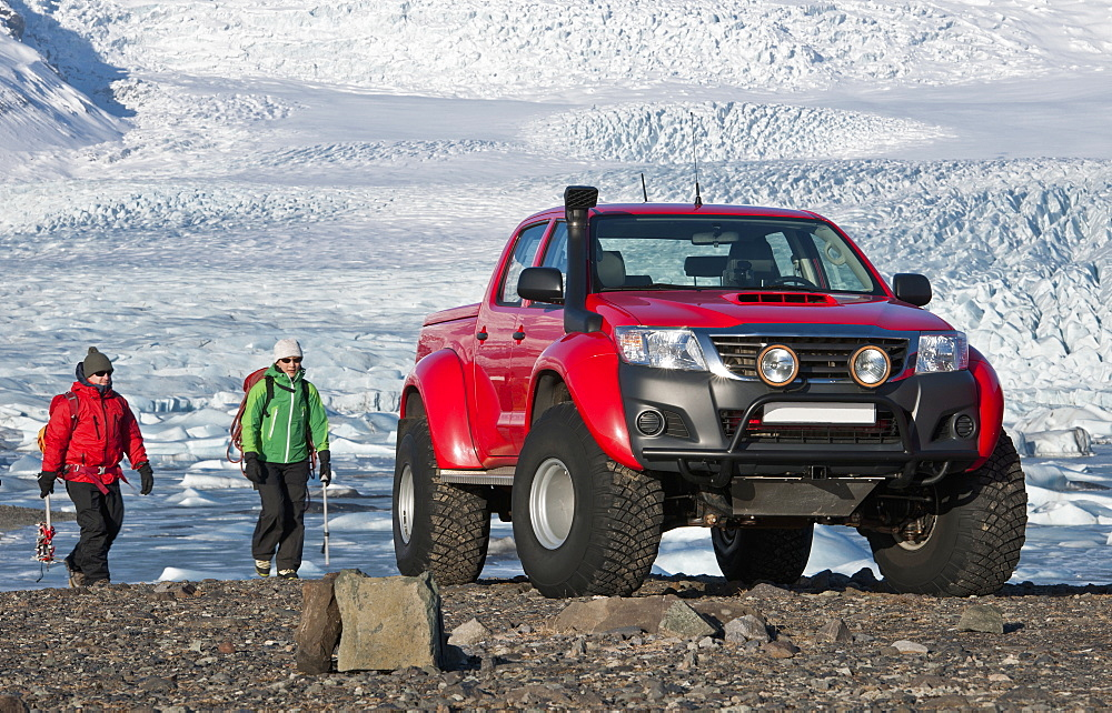 2 climbers hiking back to customised SUV / Icelandic superjeep / 4x4 pick up truck