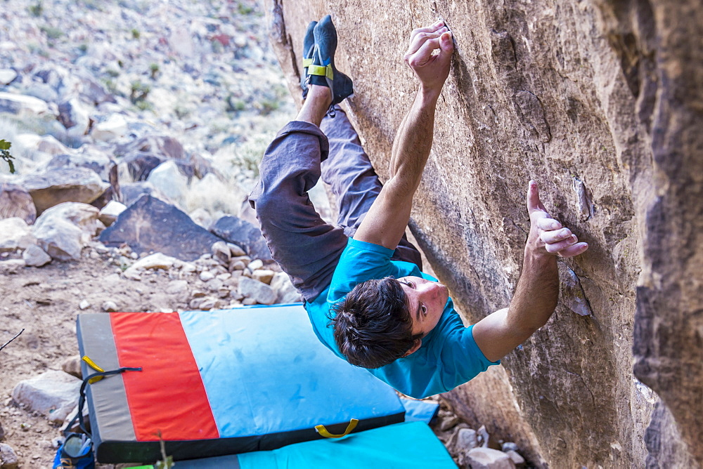 Male rock climber tries difficult boulder problem in Red Rock National Park, outside Las Vegas, Nevada