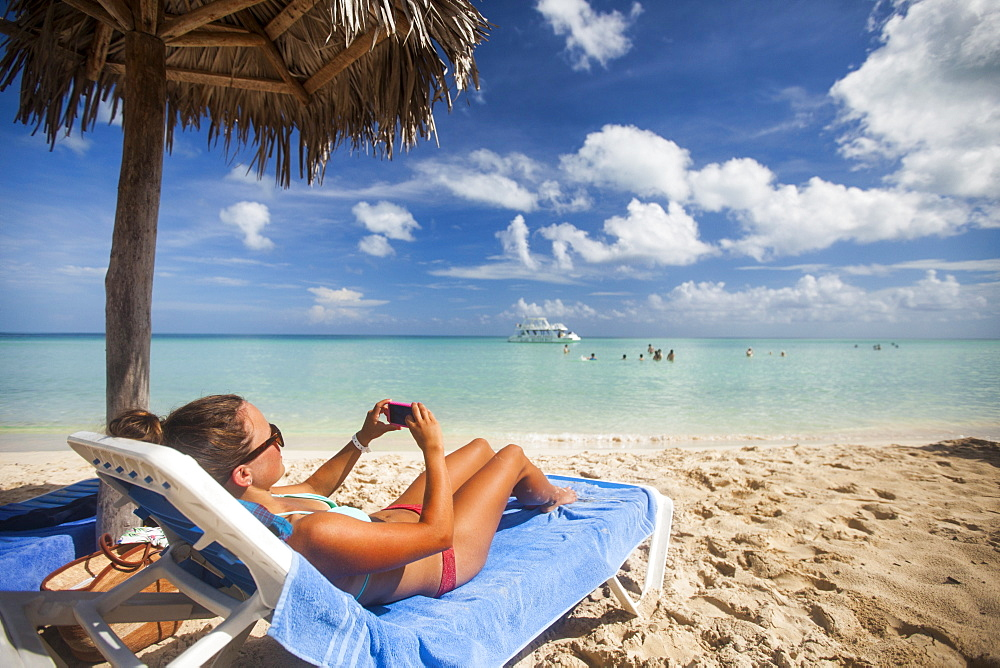 A young woman takes a picture with her smartphone while relaxing on the beach during a vacation in Cayo Coco, Cuba.