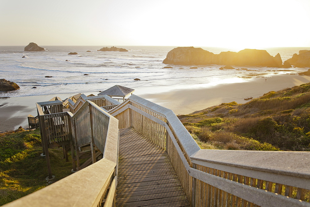 Evening light shines on a long wooden staircase leads down to Bandon Bay on the Oregon Coast.