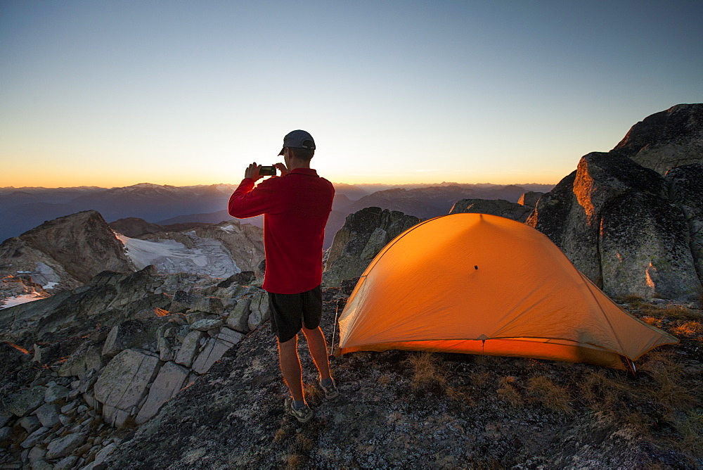 A hiker takes a picture of the sunset with his smartphone while camping on the summit of Saxifrage Peak, Pemberton, BC, Canada.