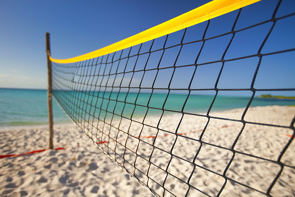A beach volleyball net set up beside the ocean on Playa La Jaula beach, Cayo Coco, Cuba.