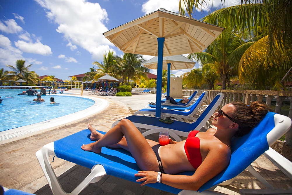 A young woman wearing a bikini and holding a drink relaxes beside a pool while on vacation in Cayo Coco, Cuba.