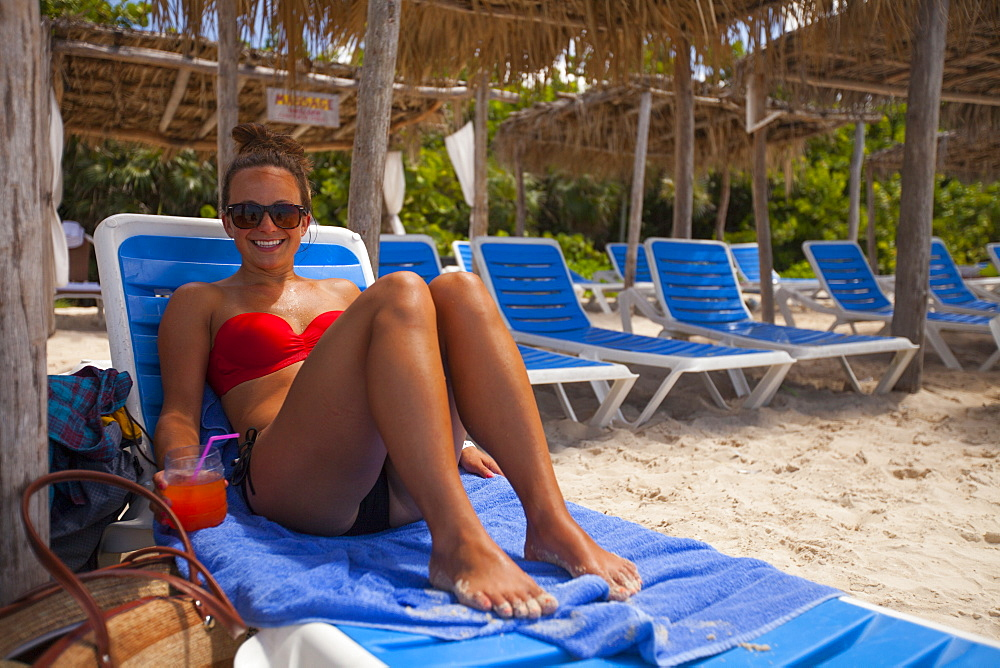 A young woman wearing a bikini and holding a drink relaxes at the beach while on vacation in Cayo Coco, Cuba.