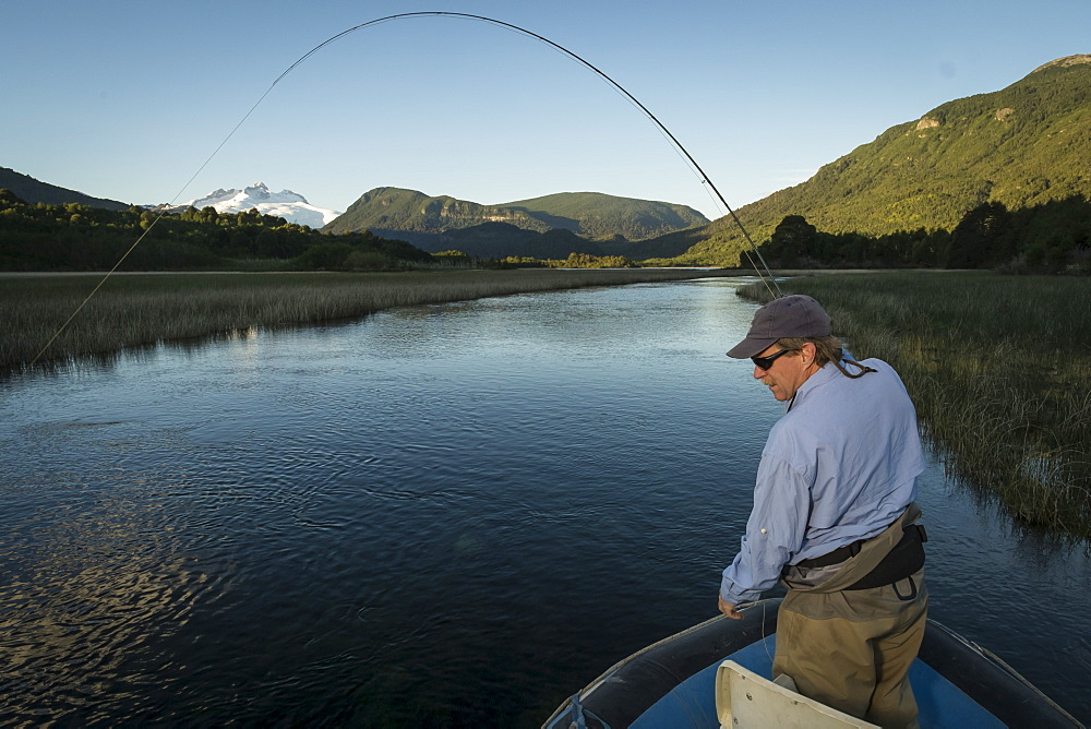 Fly fisherman catching a trout on Rio Manso in Nahuel Huapi National Park near Bariloche, Argentina.