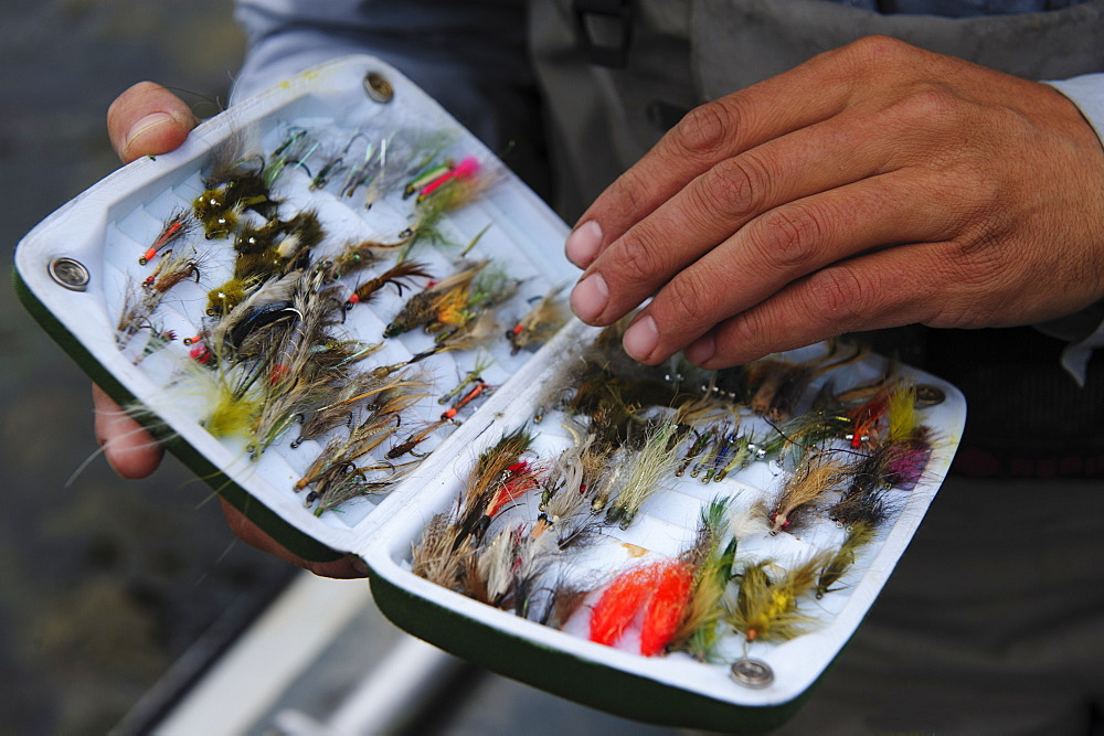 A fly fisherman examines his fly box.