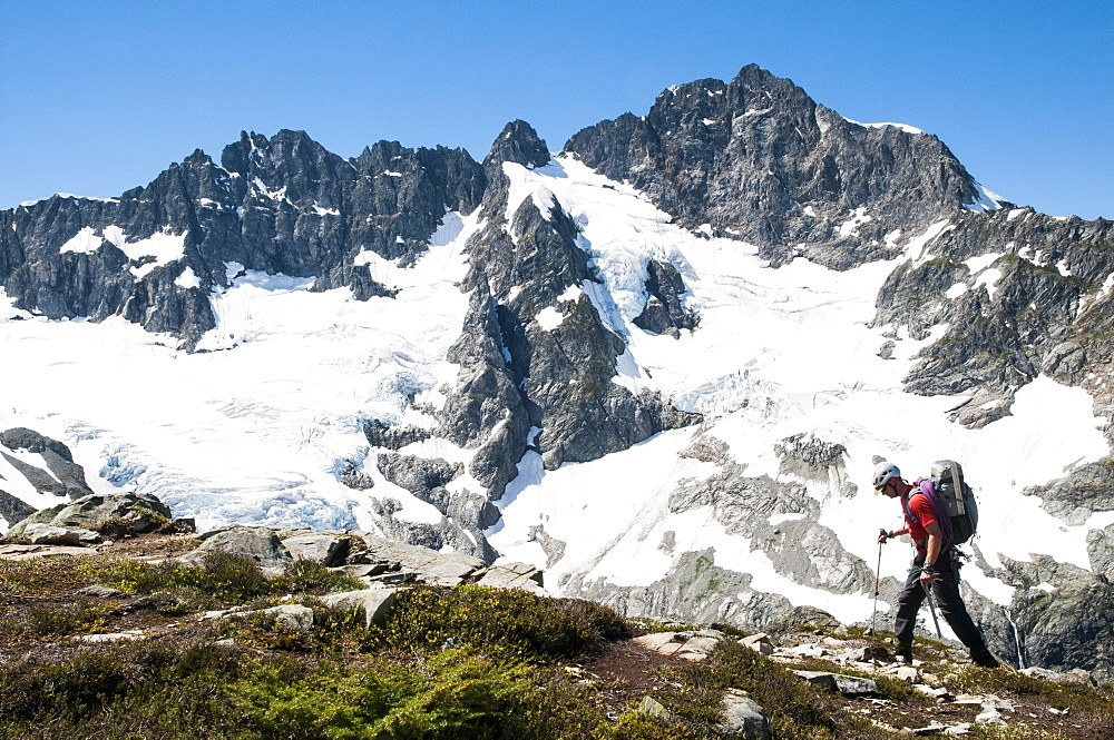 Climber traversing in front of Mount Formidable during the Ptarmigan Traverse , North Cascades, Washington