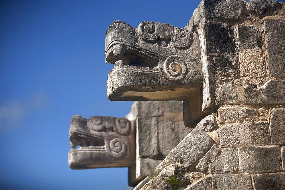 Two heads representing Kukulkan, the Feathered Serpent god, decorate a building in the Mayan city of Chichen Itza, Yucatan Peninsula, Mexico