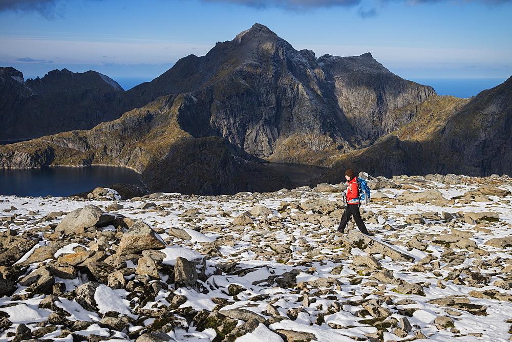 Female hiker on the rocky summit of Munken after a light autumn snow, Moskenesøy, Lofoten Islands, Norway