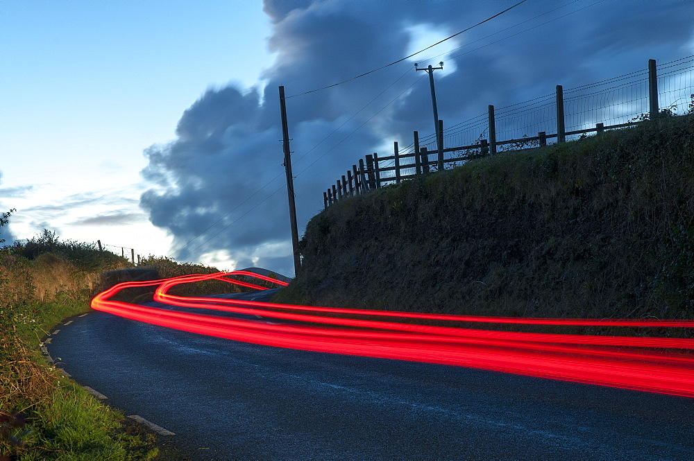 Car streaks on the narrow hillside roads of Dingle