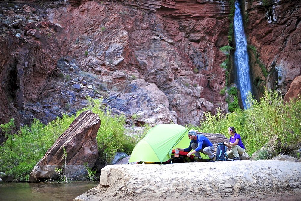 Hikers setup camp on a beach along the Colorado River near the plumeting 180-foot Deer Creek Falls in the Grand Canyon outside of Fredonia, Arizona November 2011.  The 21.4-mile loop starts at the Bill Hall trailhead on the North Rim and descends 2000-feet in 2.5-miles through Coconino Sandstone to the level Esplanada then descends further into the lower canyon through a break in the 400-foot-tall Redwall to access Surprise Valley.  Hikers connect Thunder River and Tapeats Creek to a route along the Colorado River and climb out Deer Creek.