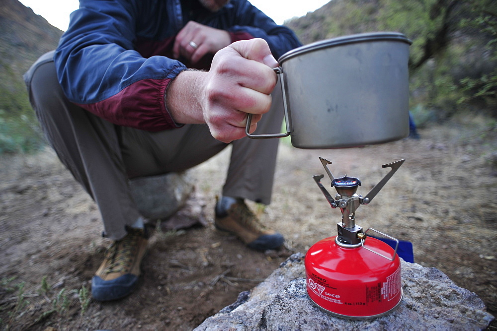 Woman and man backpackers prepare dinner with a camp stove at camp close to Charleboise Springs in La Barge Canyon on the Dutchmans Trail in the Superstition Wilderness Area, Tonto National Forest near Phoenix, Arizona November 2011.  The trail links up with the popular Peralta Trail and offers a spectacular tour through the rugged Sonoran desert.