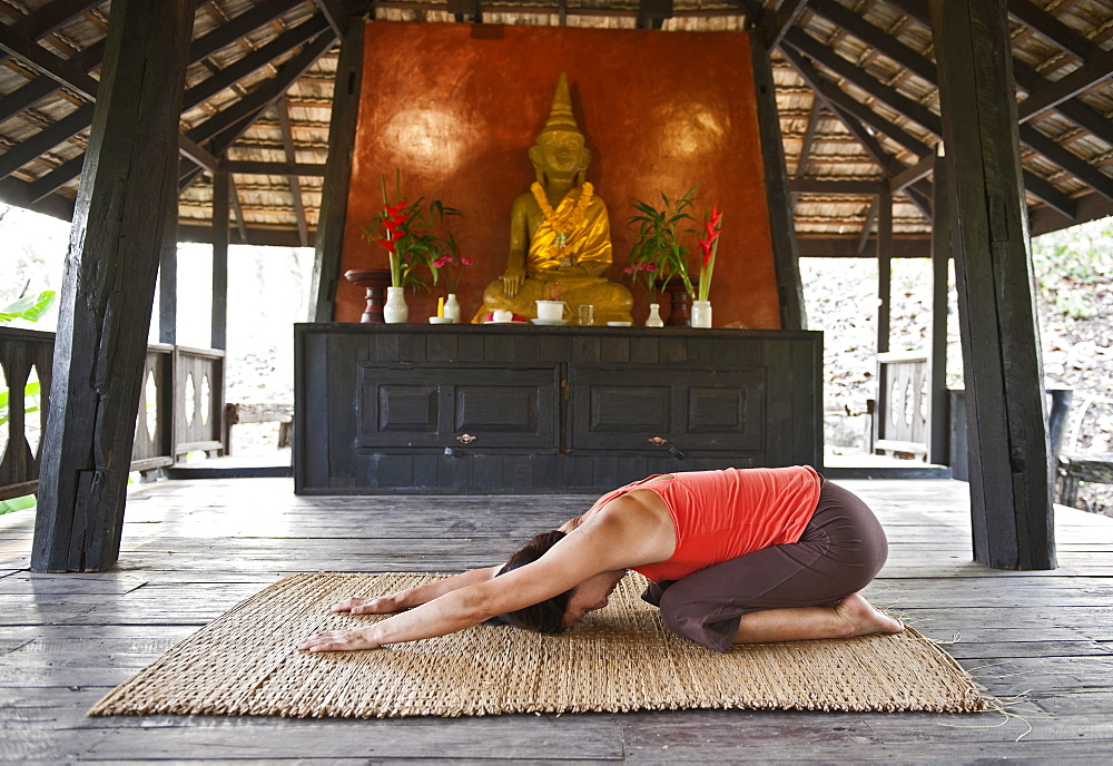 Woman doing yoga at traditional Thai House
