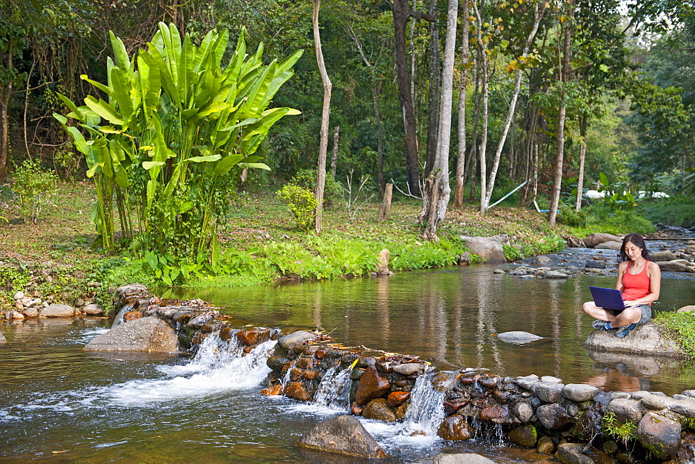 Woman sitting at a waterfall with her laptop by a small pond in northern Thailand