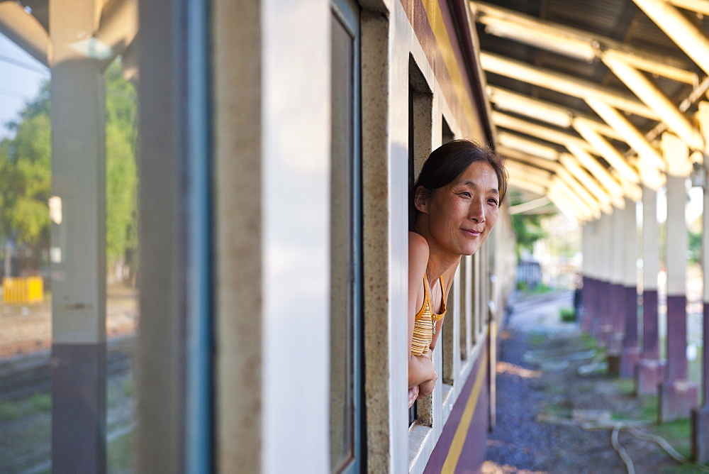 woman leaning out of train window in Chiang Mai in northern Thailand - 857-89767