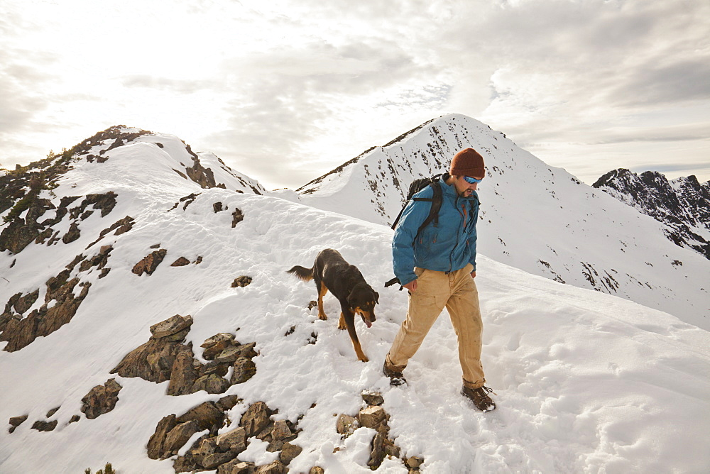A hiker and his dog descend from  the summit of Frosty Peak in Manning Provincial Park, British Columbia, Canada.