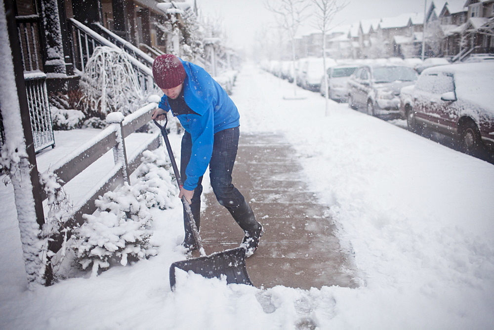 A man shovels the sidewalk outside of his suburban house during a snow storm.