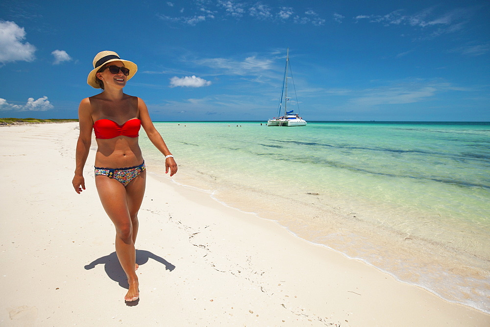 A young woman wearing a bikini and sun hat walks a sandy beach while on vacation in Cuba.