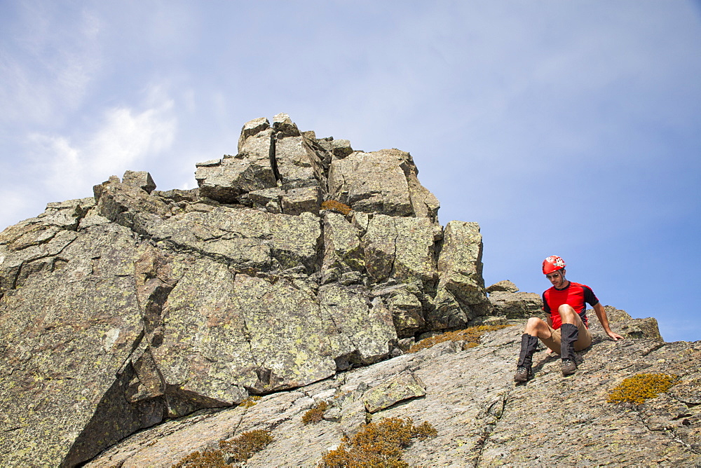 A climber down climbs a rocky summit in British Columbia, Canada.