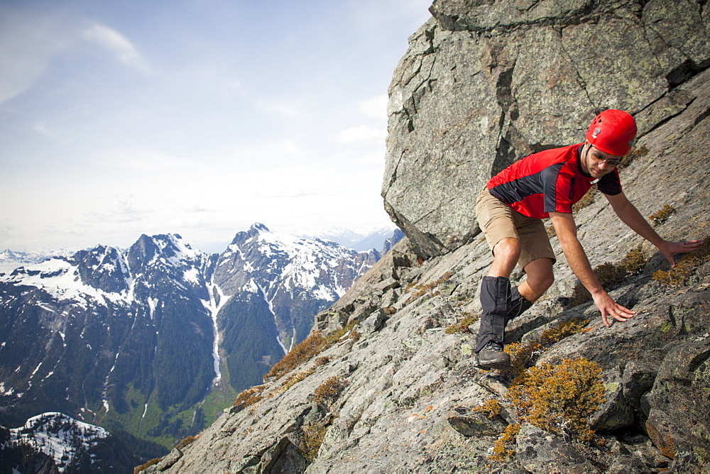 A climber carefully crosses a steep rock slab near the summit of Trio Peak, British Columbia, Canada.