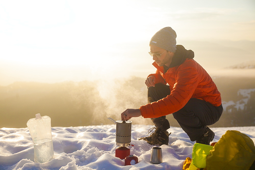 A climber attends to his boiling water on a camping stove while camping in the mountains of British Columbia, Canada.