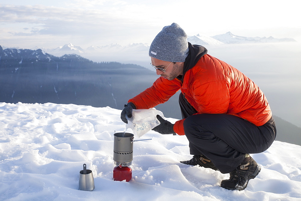 A climber pours water into a camping stove while camping in the mountains of British Columbia, Canada.