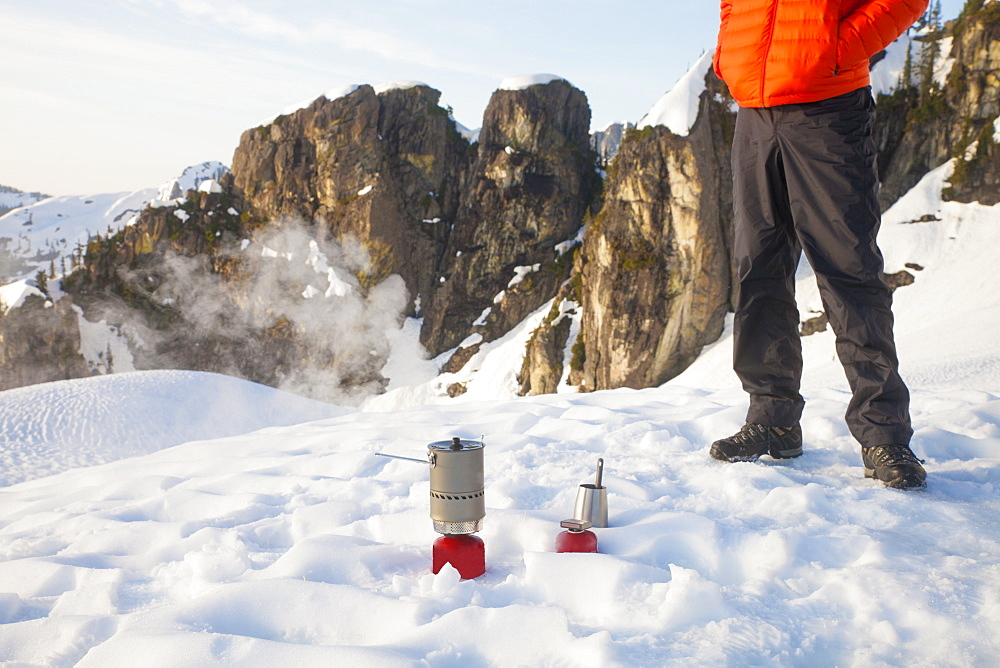 A climber attends to his camping stove while camping in the mountains of British Columbia, Canada.