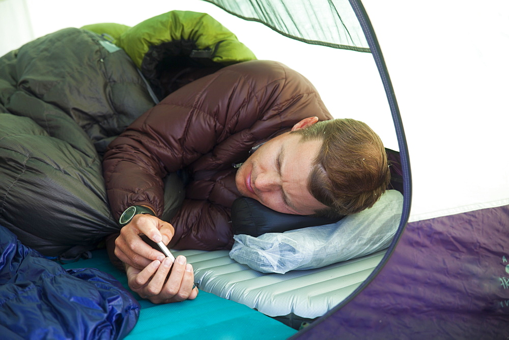 A climber checks his e-mail from his tent while camping in the mountains of British Columbia, Canada.