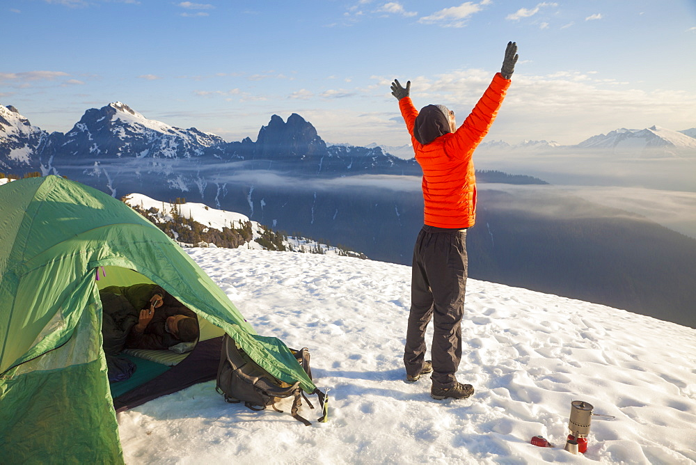 A climber celebrates the beautiful day he woke up to while camping in the mountains of British Columbia, Canada.