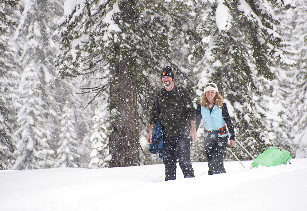 Smiling man and woman snowshoeing in snow storm, Sierra Nevada - 857-89938