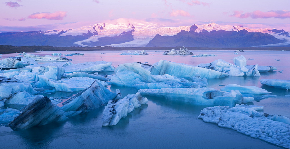 Icebergs near the mouth of Jökulsárlón Glacier Lagoon at sunrise in Southern Iceland.