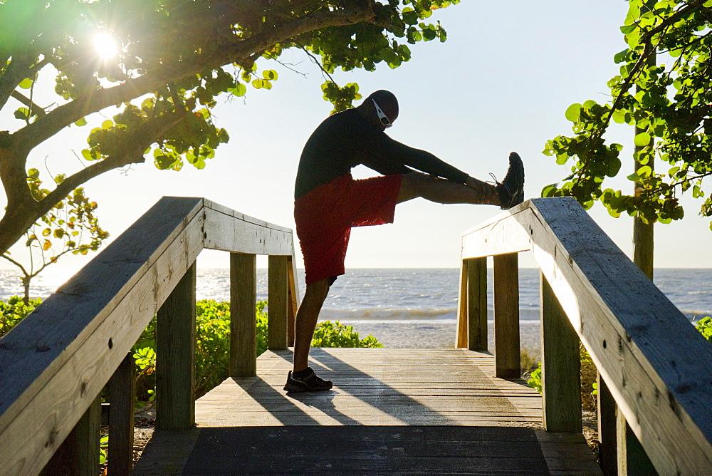 Man stretching on a beach boardwalk