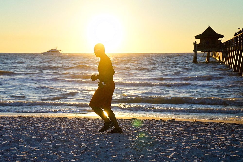 Man jogging on the beach at sunset with a yacht on the horizon and a pier in the background