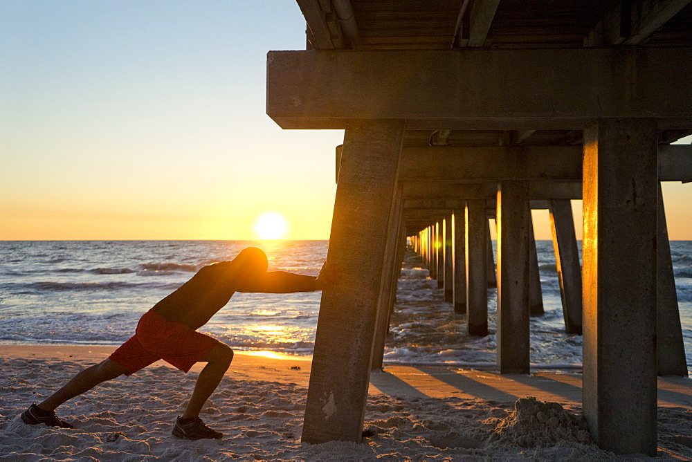 Man stretching, using a pier pillar on the beach at sunset