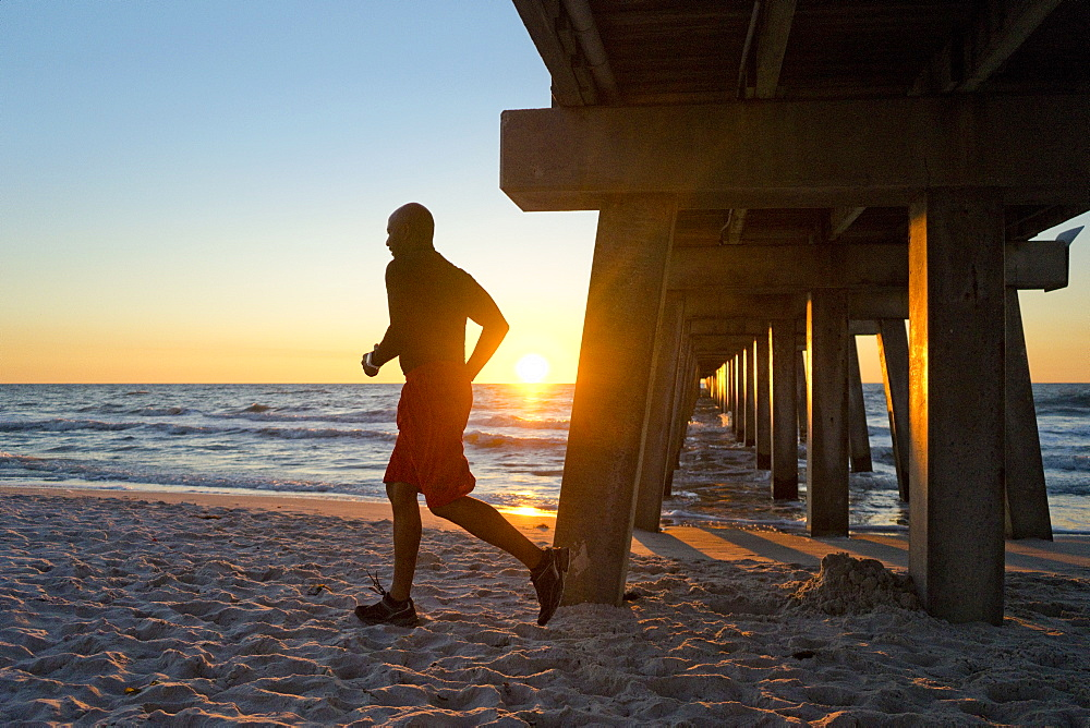 Man running under a pier on the beach at sunset