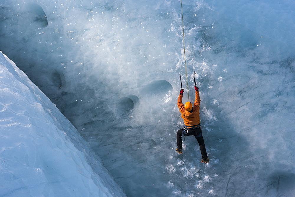 Man climbing a steep glacier ice at the glacier Gigjokull. South Iceland.