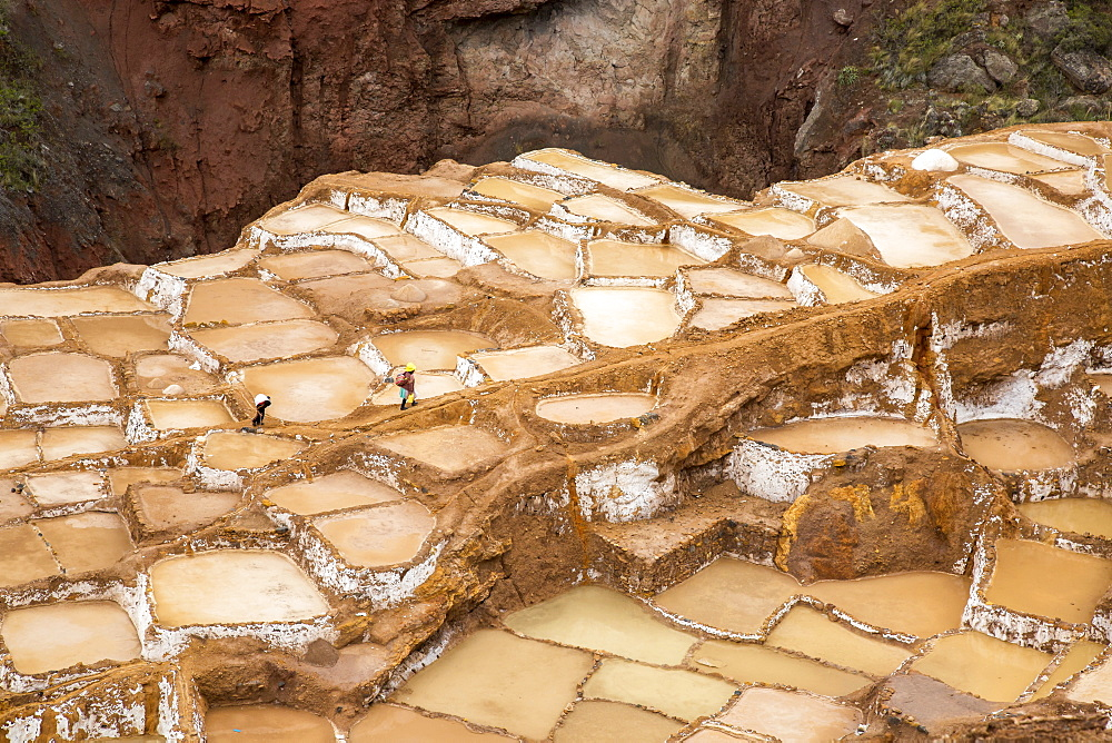 Salt workers walk across the Salinas salt pools in the Sacred Valley, Peru. - 857-90391