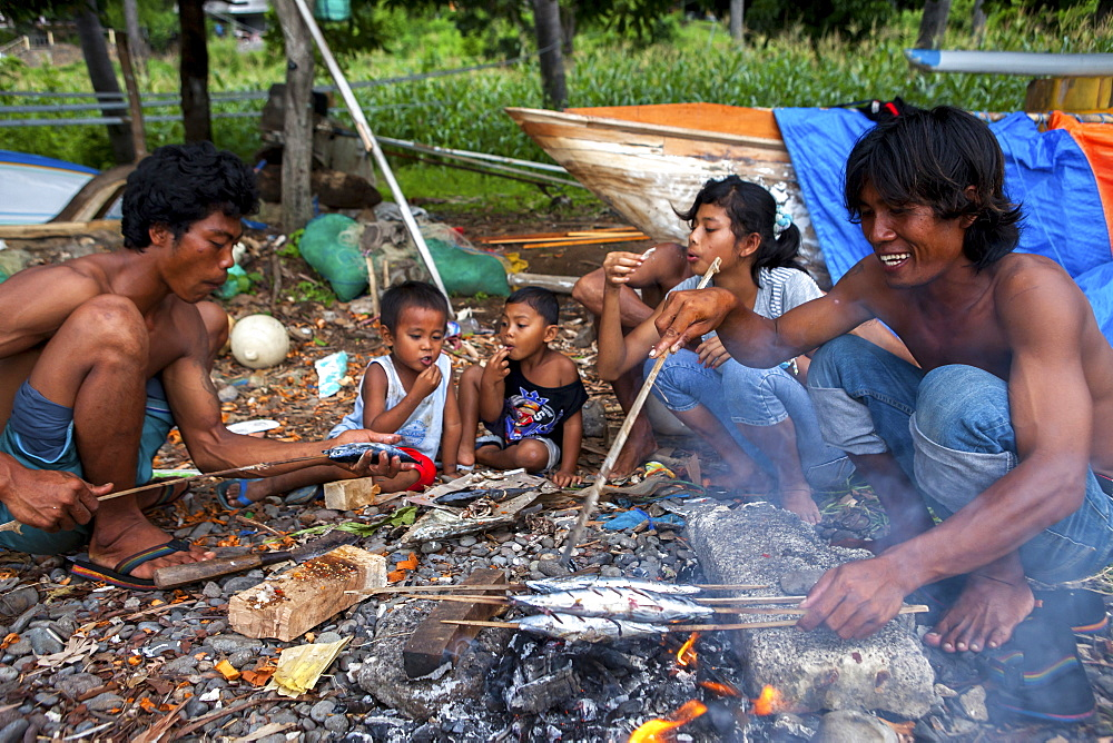 A fisherman?s family eats after cooking the fish they caught in the town of Amed in Bali, Indonesia. - 857-90411