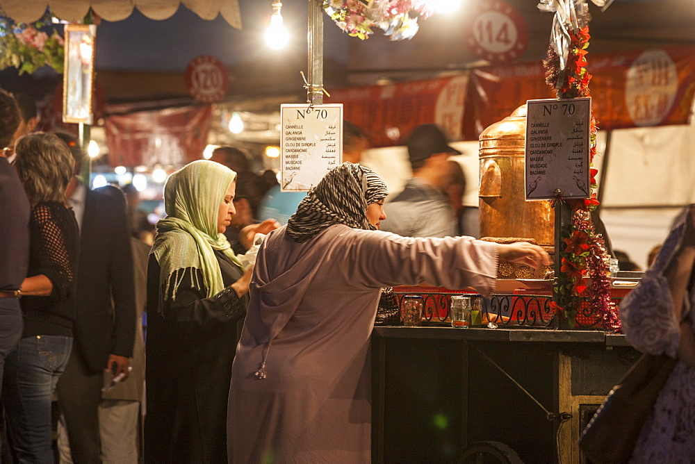 Two Women (40-50-60 years old) with the typical arabic dress (djellaba) at a food stall in Jemaa EL Fna square in Marrakesh, Morocco.