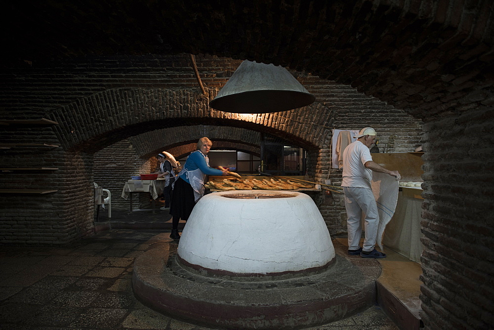 Adjaruli khachapuri bread makers bake traditional Geogian bread in the basement of a building located in the city of Tbilisi, Republic of Georgia.